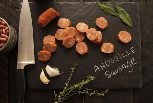 Andouille Sausage on Black Cutting Board